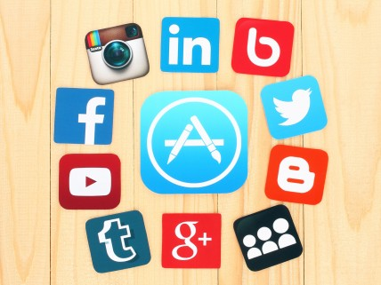 45701275 - kiev, ukraine - july 01, 2015: around appstore icon are placed famous social media icons such as: facebook, twitter, blogger, linkedin and others, printed on paper and placed on wooden background.